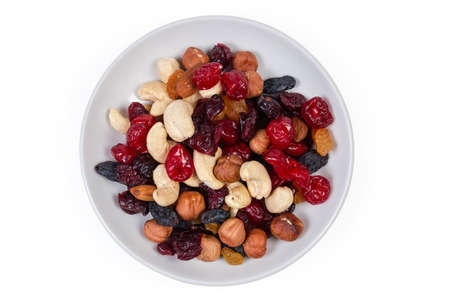 Mix of different nuts, dried fruits and berries on the white saucer on a white background, top view 版權商用圖片