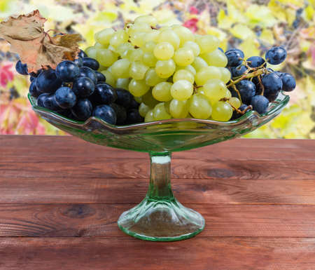 Clusters of ripe table blue grapes and white seedless sultana grapes in the vintage green glass vase for fruits on the rustic table on a blurred background Banco de Imagens