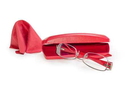 Modern eyeglasses for women in metal yellow with red rim against the partly open red hard spectacle-case and wipe for glasses on a white background, close-up in selective focus