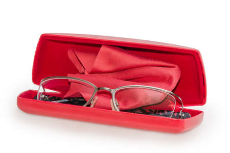 Modern eyeglasses for women in metal rim in the open red hard spectacle-case with red wipe for glasses on a white background, close-up in selective focus