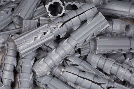 Pile of gray plastic split-ribbed anchors, also known as conical screw anchors close-up, background