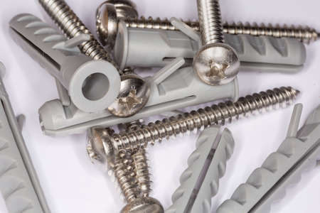 Pile of cross recessed pan head tapper screws with silvery corrosion coating and appropriate plastic split-ribbed anchors, close-up in selective focus