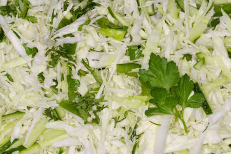 Green vegetable salad made of sliced fresh young cabbage with cucumbers, green bell pepper and chopped greens, top view, background
