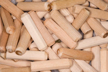 Pile of fluted wooden dowel pins close-up, top view, background Imagens