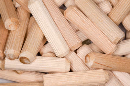 Pile of fluted wooden dowel pins, fragment close-up, background Imagens