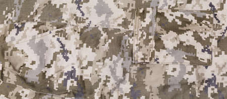 Fragment of pants made of pixellated digital camouflage fabric of dull olive-green color with two different pockets, background