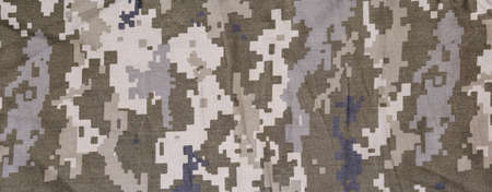 Fragment of slightly crumpled fabric with pixellated digital camouflage pattern dull olive-green and gray color. Panoramic view, background, texture