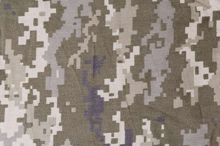 Fragment of slightly crumpled fabric with pixellated digital camouflage pattern dull olive-green and gray color close-up. Background, texture