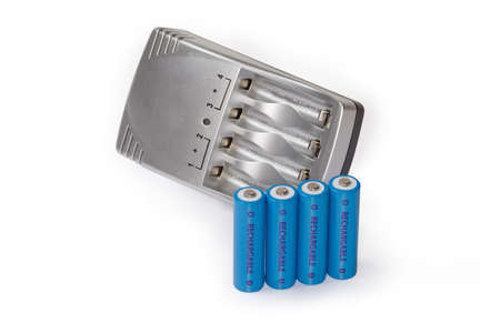 Rechargeable batteries AA size against the smart battery charger on a white background