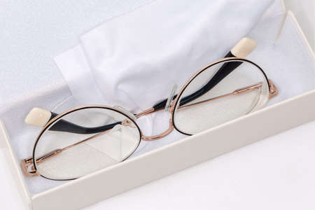 Modern eyeglasses for women in metal yellow rim lie in white hard spectacle-case with glasses wipe, close-up in selective focus 스톡 콘텐츠