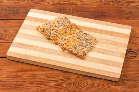 Flat rectangular crispy cookies made with puff pastry, sprinkled with sesame, flax and sunflower seeds on bamboo cutting board on an old rustic table 스톡 콘텐츠