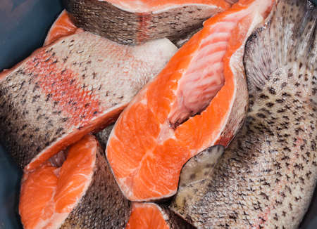 Fresh uncooked rainbow trout cut into pieces in a kitchen bowl close-up, top view, background 스톡 콘텐츠