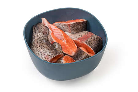 Pieces of fresh uncooked rainbow trout in a kitchen plastic bowl on a white background