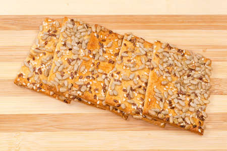 Few flat rectangular crispy cookies made with puff pastry, sprinkled with sesame, flax and sunflower seeds on bamboo board close-up