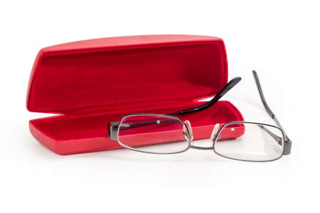 Modern eyeglasses in metal gray rim with open temples against the red hard spectacle-case on a white background, close-up in selective focus