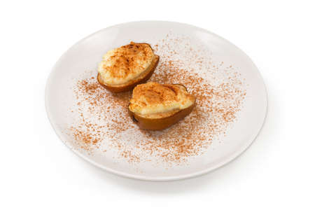 Baked pears halves with ricotta cheese filling, sprinkled with cinnamon powder on a white dish on a white background 스톡 콘텐츠