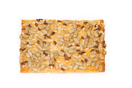 Single flat rectangular crispy cookie made with puff pastry, sprinkled with sesame, flax and sunflower seeds on a white background, top view, background 스톡 콘텐츠
