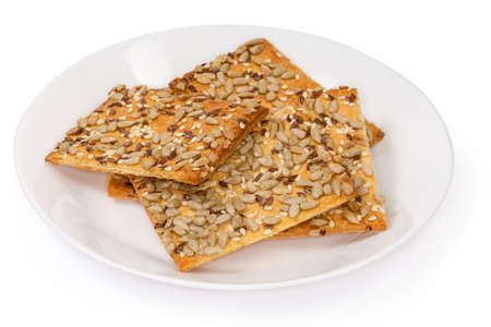 Flat rectangular crispy cookies made with puff pastry, sprinkled with sesame, flax and sunflower seeds on a white dish on a white background, close-up in selective focus
