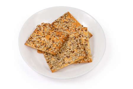 Flat rectangular crispy cookies made with puff pastry, sprinkled with sesame, flax and sunflower seeds on a white dish on a white background 스톡 콘텐츠