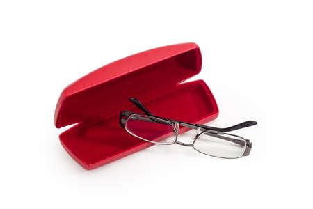 Modern eyeglasses in metal gray rim with folded temples against the red hard spectacle-case on a white background 스톡 콘텐츠
