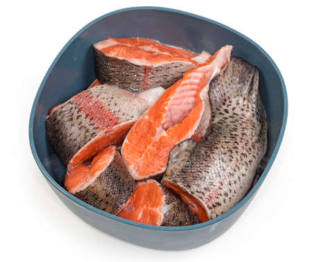 Fresh uncooked rainbow trout cut into pieces in a kitchen plastic bowl on a white background, top view