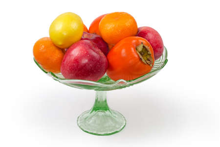 Different fresh fruits in a vintage green glass vase for fruits on a leg on a white background 스톡 콘텐츠