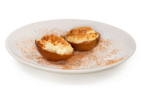 Baked pears halves with ricotta cheese filling, sprinkled with cinnamon powder on a white dish on a white background, close-up