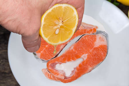 Lemon half in hand during juice squeezing on to the trout pieces for their preparation, top view close-up