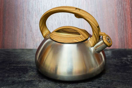 Matt stainless steel stovetop kettle with closed steam whistle on a spout, plastic lid and handle on a dark surface Stock fotó