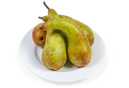 Ripe greenish-brown pears of Conference variety on a white plate on a white background