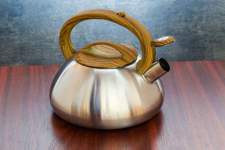 Stainless steel stovetop kettle with steam whistle built-in in spout on a wooden table Stock fotó