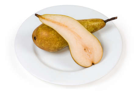 One half and one whole ripe yellow pears of the Conference variety on a white plate on a white background