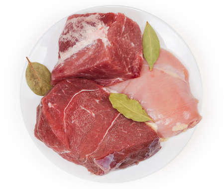 Big pieces of uncooked boneless pork and beef of hind leg, chicken with bay leaves on a white dish on a white background, top view