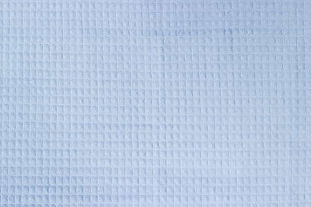 Texture of the fabric of a light blue cotton waffle towel with horizontal layout of pattern, top view, background