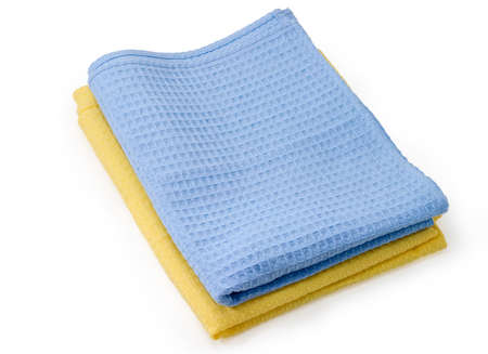 One blue and one yellow folded cotton waffle towels in a stack on a white background
