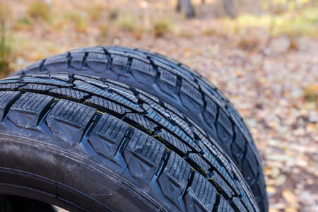Aggressive non-symmetrical tread of car winter tires. Fragment of the new tires on a blurred background, close-up at selective focus