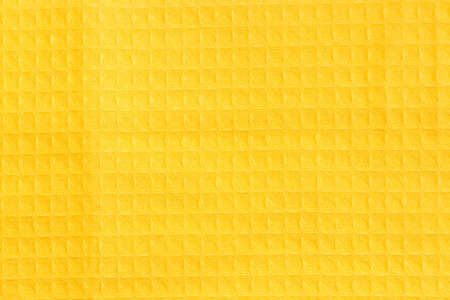 Texture of the fabric of a yellow cotton waffle towel with horizontal layout of pattern, top view close-up