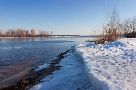 Section of wide plain river partially covered with thin ice, thick ice floes on the shore on a foreground against the clear sky and forest on opposite bank in early springtime