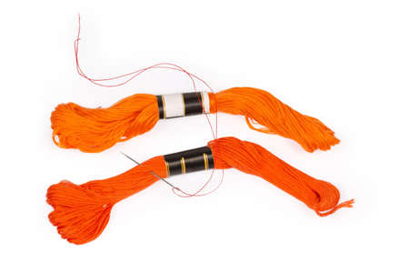 Two skeins of the cotton stranded embroidery floss orange color of different shades and hand sewing needle with a tucked red thread on a white background