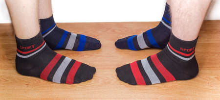 Black socks with different color of the ornament on the two mens legs on a wooden floor against a light background