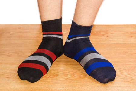 Pair of black socks with different color of the ornament on the men foots on a wooden floor against a white background