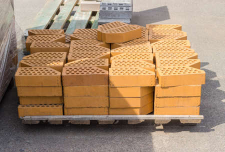 Yellow perforated decorative face bricks with an oblique one angle stacked on wooden pallet on an outdoor warehouse