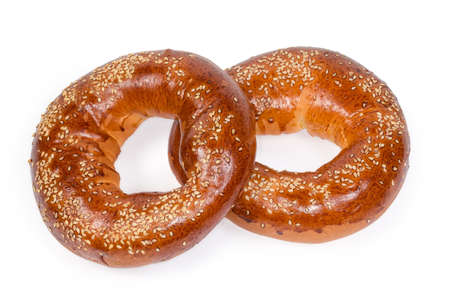 Two traditional Eastern European ring shaped bread rolls sprinkled with sesame seeds before being baked on a white background