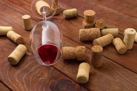 Wine glass lying on its side with small leftover red wine among the different used corks on an old rustic table