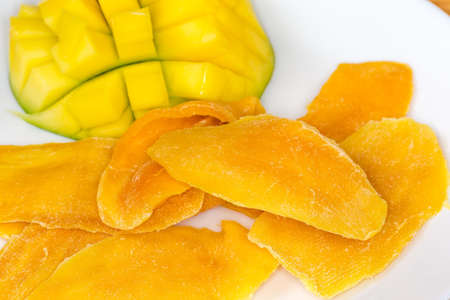 Dried slices of mango pulp against the fresh cut mango half, close-up in selective focus