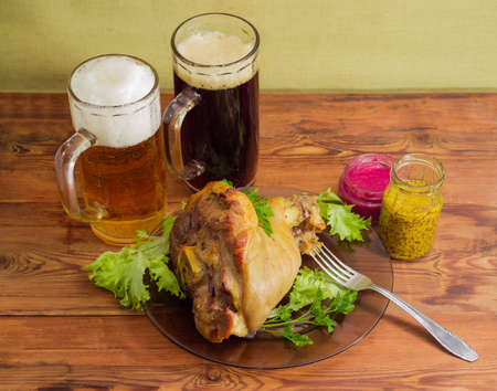 Serving of baked ham hock with lettuce and parsley on glass dish with fork, two beer glasses of dark and lager beer, condiment on an old wooden rustic table