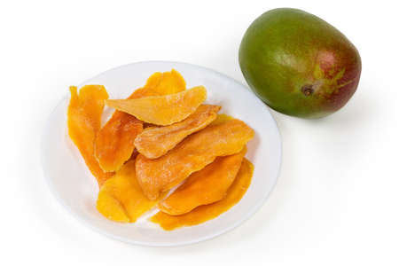 Dried slices of mango pulp on white dish and whole fresh mango on a white background