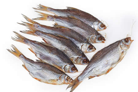 Several salted and air-dried roach fish on string on a white background, top view