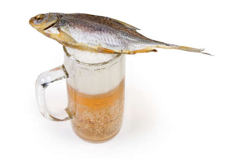Salted and air-dried roach fish lies on a beer glass partially filled with lager beer on a white background