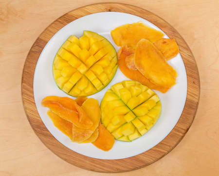 Dried slices of mango pulp and fresh mango halves cut in form the hedgehog style on white dish on a wooden surface, top view